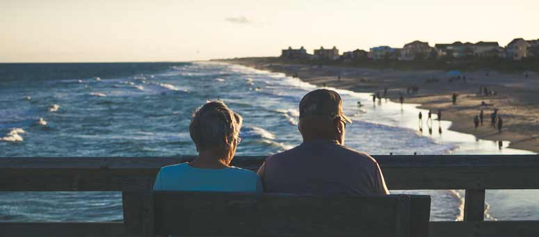 Old couple sitting on bench in front of beach